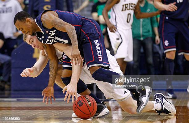 Scott Martin of the Notre Dame Fighting Irish and Ryan Boatright of the Connecticut Huskies battle for a loose ball at Purcel Pavilion on January 12...