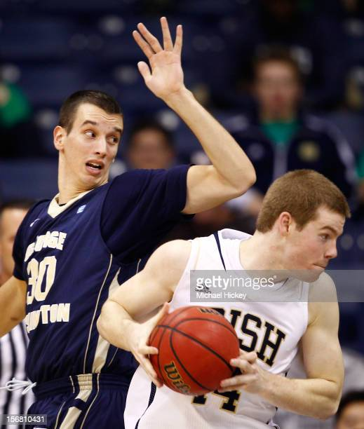 Scott Martin of the Notre Dame Fighting Irish makes a move to the basket as Nemanja Mikic of the George Washington Colonials defends at Purcel...