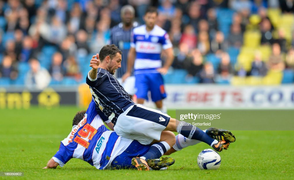 Scott McDonald of Millwall FC is tackled by Niko Kranjcar of Queens Park Rangers during the Sky Bet Championship match between Millwall and Queens...