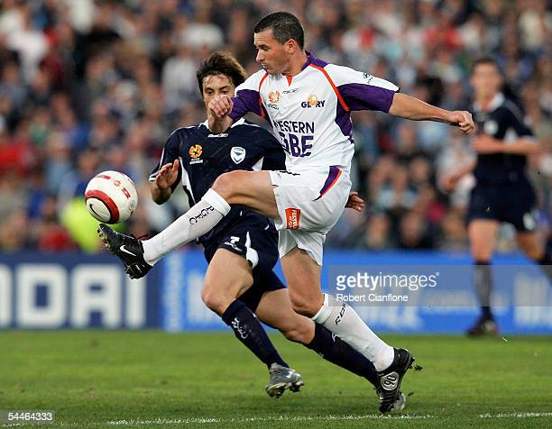 Scott Miller of the Glory gets to the ball ahead of Michael Ferrante of the Victory during the round two ALeague match between Melbourne Victory and...