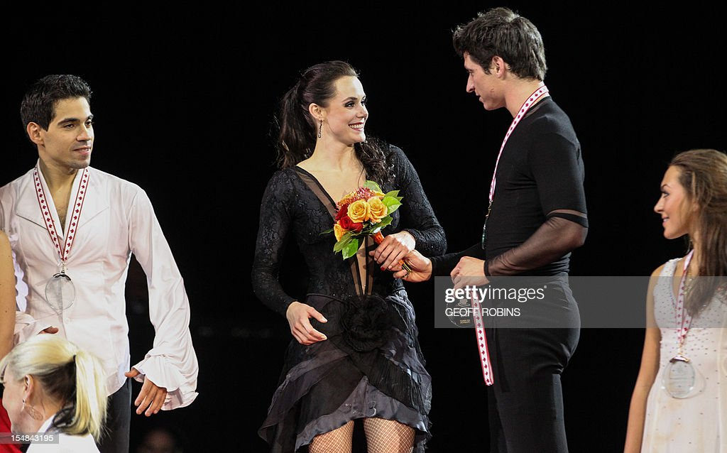 Scott Moir of Canada gives his partner Tessa Virtue her flowers and gold medal after she had to step out of the awards ceremony at the 2012 Skate Canada International ISU Grand Prix event in Windsor on October 27, 2012. AFP PHOTO/Geoff Robins