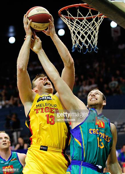 Scott Morrison of the Tigers attempts a layup past Greg Vanderjagt of the Crocodiles during the round 12 NBL match between the Townsville Crocodiles...
