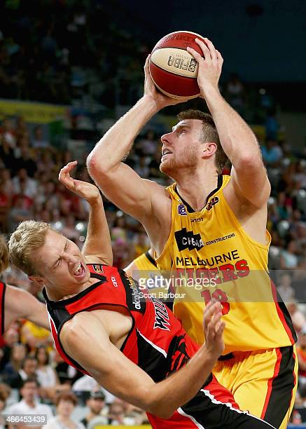 Scott Morrison of the Tigers fouls Shawn Redhage of the Wildcats as he attempts to shoot the ball during the round 16 NBL match between the Melbourne...