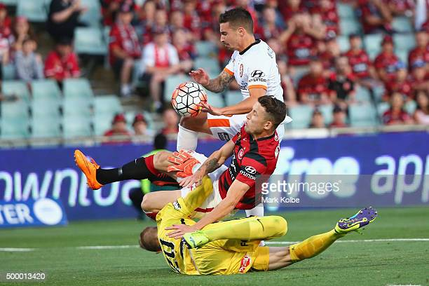 Scott Neville and Andrew Redmayne of the Wanderers tackle Jamie Maclaren of the Roar as he shoots at goal during the round nine ALeague match between...