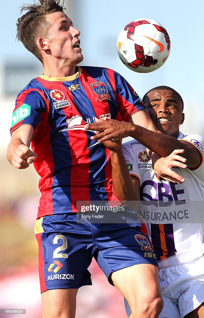 Scott Neville of the Jets headers the ball against Sidnei Sciola Moraes of the Glory during the round two A-League match between the Newcastle Jets and the Perth Glory at Hunter Stadium on October 20, 2013 in Newcastle, Australia.