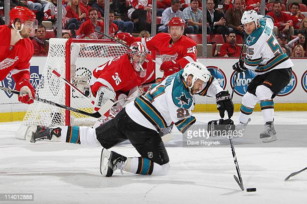 Scott Nichol of the San Jose Sharks controls the puck while Brian Rafalski of the Detroit Red Wings and teammate Jimmy Howard defend the net during...