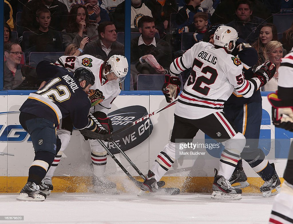 Scott Nichol of the St Louis Blues and Michael Frolik of the Chicago Blackhawks battle for a loose puck along the boards in an NHL game on February...