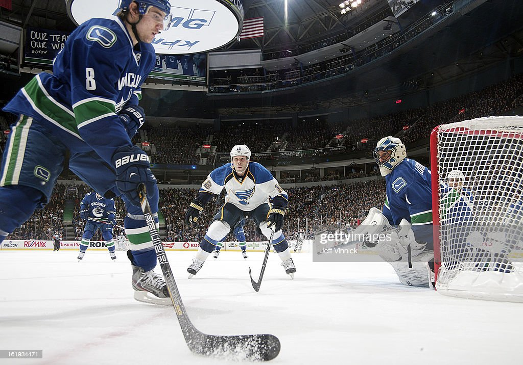 Scott Nichol of the St Louis Blues and Roberto Luongo of the Vancouver Canucks watch Christopher Tanev of the Canucks play the puck during their NHL...
