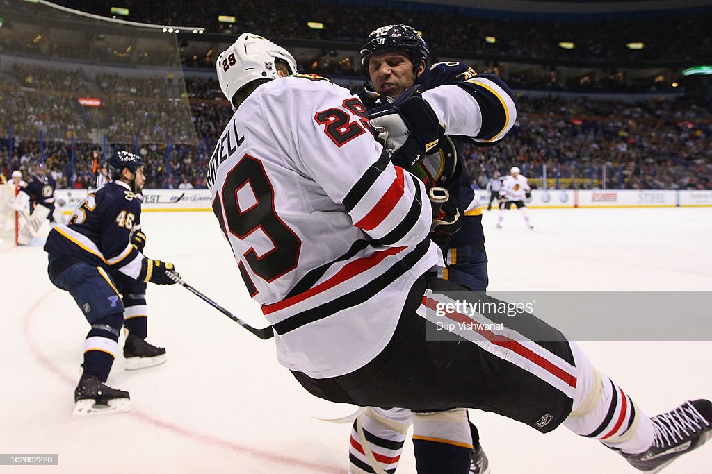 Scott Nichol of the St Louis Blues checks Bryan Bickell of the Chicago Blackhawks at the Scottrade Center on February 28 2013 in St Louis Missouri