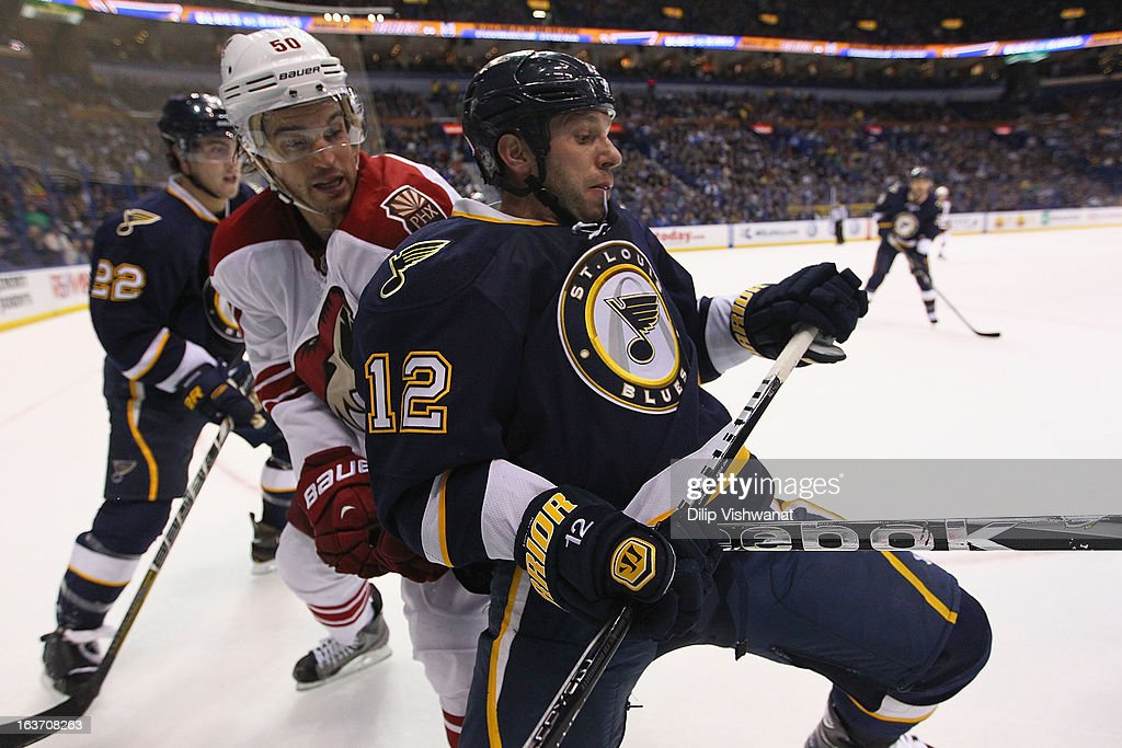 Scott Nichol of the St Louis Blues holds Antoine Vermette of the Phoenix Coyotes off the puck at the Scottrade Center on March 14 2013 in St Louis...