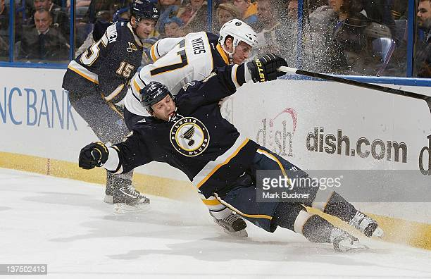 Scott Nichol of the St Louis Blues slips and slams into the boards as Tyler Myers of the Buffalo Sabres skates after the puck in an NHL game on...