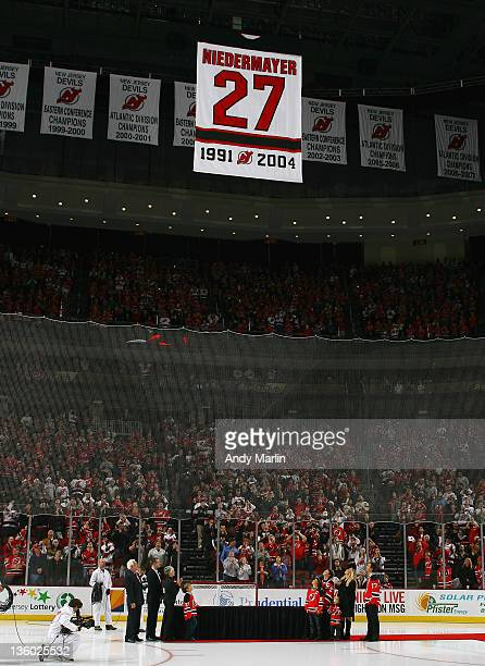 Scott Niedermayer and his family watch his number 27 jersey raised to the rafters during the retirement ceremony prior to the game between the New...