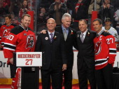 Scott Niedermayer is joined by Martin Brodeur Ken Daneyko Larry Robinson and Scott Stevens during his jersey retirement ceremony by the New Jersey...