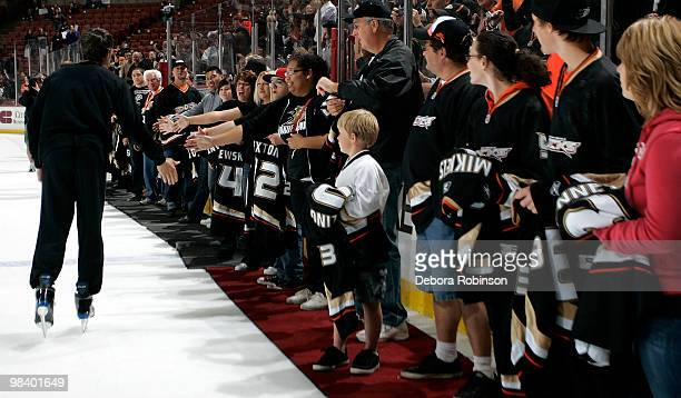 Scott Niedermayer of the Anaheim Ducks high fives fans during the 'shirt of their backs' for the fans after the game against the Edmonton Oilers on...