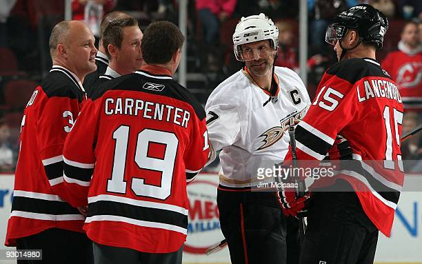 Scott Niedermayer of the Anaheim Ducks shakes hands with former teammate Bobby Carpenter prior to their NHL game as former player Ken Daneyko and...