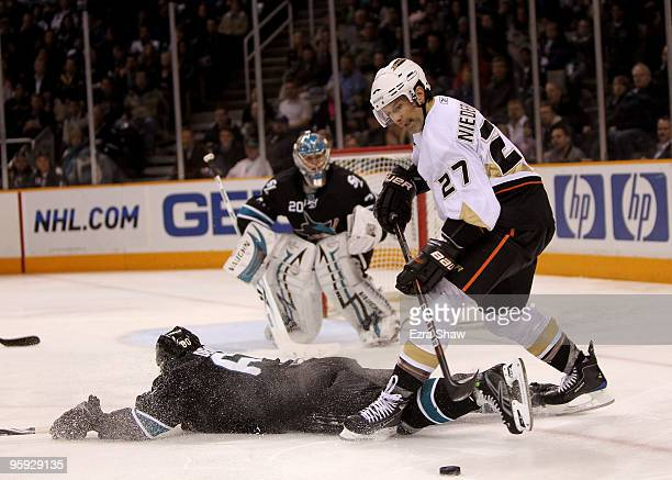 Scott Niedermayer of the Anaheim Ducks tries to control the puck with a sliding Jason Demers of the San Jose Sharks at HP Pavilion on January 21 2010...