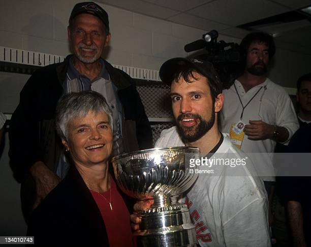 Scott Niedermayer of the New Jersey Devils celebrates in the locker room with the Stanley Cup Trophy with his mother Carol after Game 6 of the 2000...