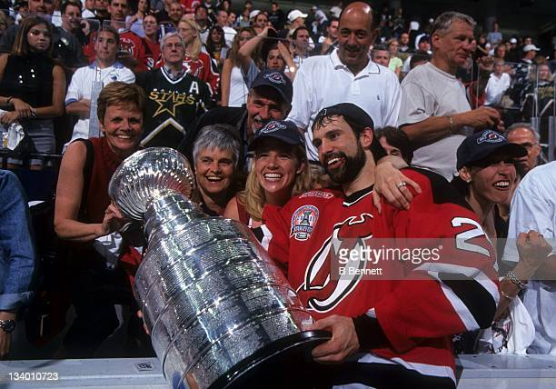Scott Niedermayer of the New Jersey Devils celebrates with the Stanley Cup Trophy with his mother Carol and wife Lisa after Game 6 of the 2000...