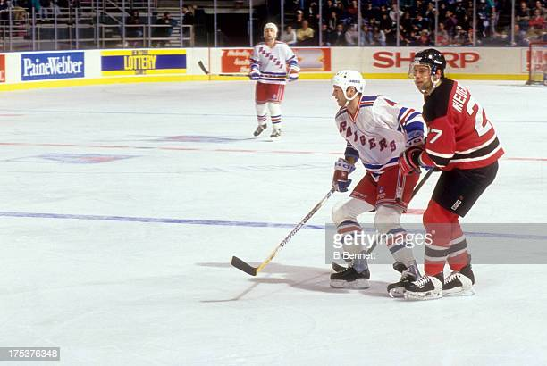 Scott Niedermayer of the New Jersey Devils follows Kevin Lowe of the New York Rangers on December 26 1993 at the Madison Square Garden in New York...