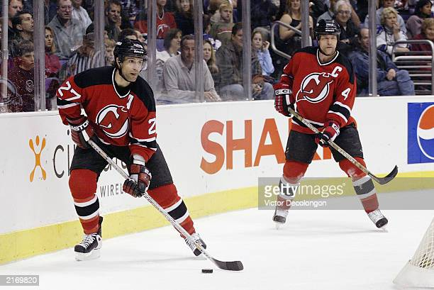 Scott Niedermayer of the New Jersey Devils looks to pass as teammate Scott Stevens looks on during the NHL game against the Los Angeles Kings at...