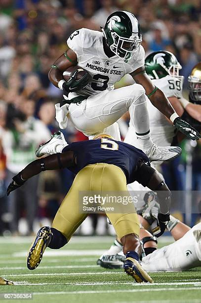 Scott of the Michigan State Spartans leaps over Nyles Morgan of the Notre Dame Fighting Irish during the first half of a game at Notre Dame Stadium...