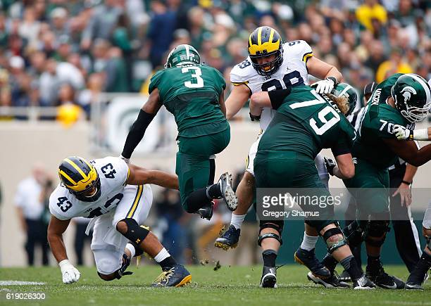 Scott of the Michigan State Spartans tries to jump between the tackles of Matthew Godin and Chris Wormley of the Michigan Wolverines during a second...