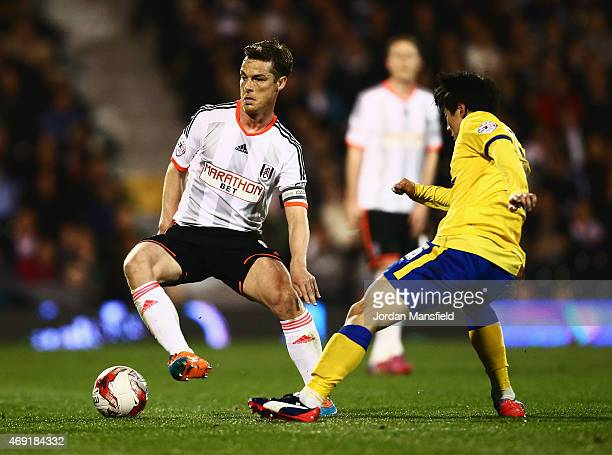 Scott Parker of Fulham evades Kim BoKyung of Wigan Athletic during the Sky Bet Championship match between Fulham and Wigan Athletic at Craven Cottage...