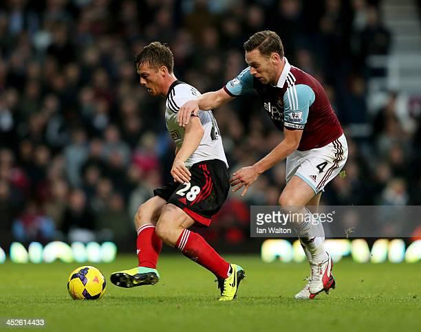 Scott Parker of Fulham holds off Kevin Nolan of West Ham United during the Barclays Premier League match between West Ham United and Fulham at Boleyn...