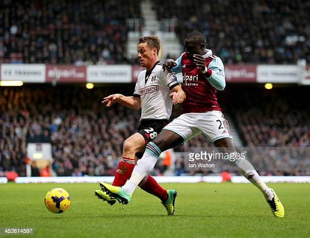 Scott Parker of Fulham holds off Mohamed Diame of West Ham United during the Barclays Premier League match between West Ham United and Fulham at...