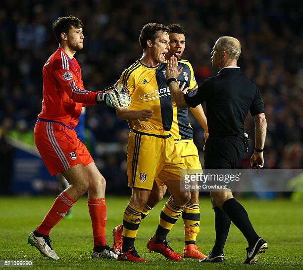 Scott Parker of Fulham is held back by teammate goal keeper Marcus Bettinelli as he exchanges words with referee Andy Woolmer after he awards a...