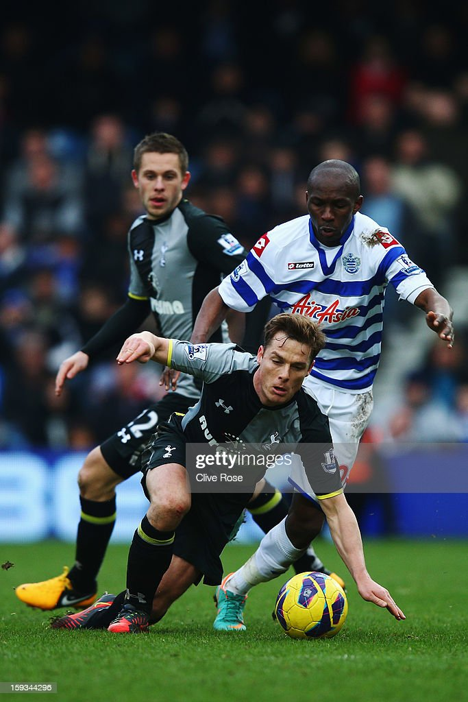 Scott Parker (L) of Tottenham Hotspur is challenged by Stephane Mbia (R) of Queens Park Rangers during the Barclays Premier League match between Queens Park Rangers and Tottenham Hotspur at Loftus Road on January 12, 2013 in London, England.