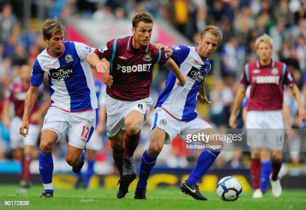 Scott Parker of West Ham is challenged by Morten Gamst Pedersen and Vince Grella of Blackburn during the Barclays Premier League match between...