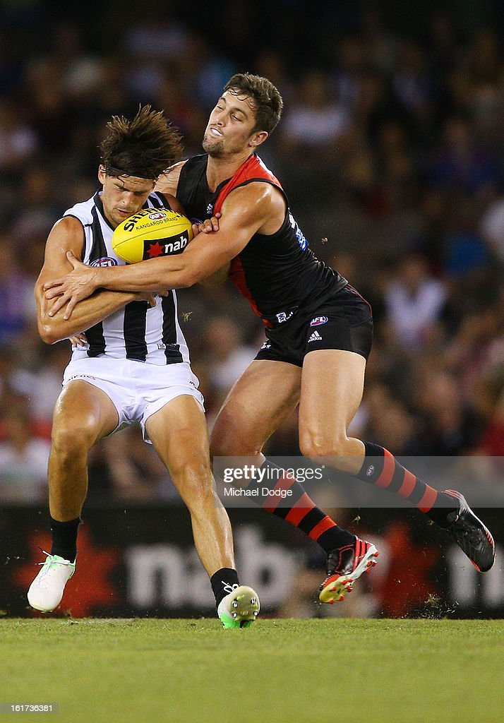 Scott Pendlebury of the Collingwood Magpies gets tackled by David Myers of the Essendon Bombers during the round one AFL NAB Cup match between the Collingwood Magpies and the Essendon Bombers at Etihad Stadium on February 15, 2013 in Melbourne, Australia.