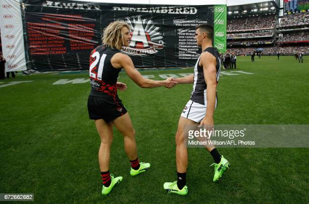 Scott Pendlebury of the Magpies and Dyson Heppell of the Bombers shake hands before running through the joint banner during the 2017 AFL round 05...