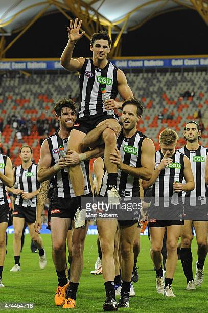 Scott Pendlebury of the Magpies is chaired from the field after playing his 200th match during the round eight AFL match between the Gold Coast Suns...