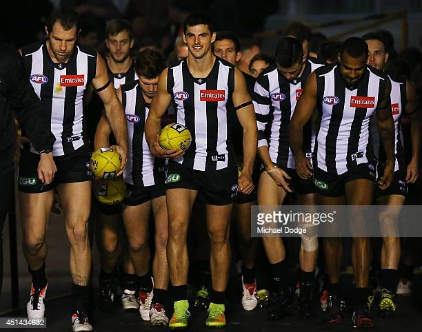 Scott Pendlebury of the Magpies leads the team out during the round 15 AFL match between the Collingwood Magpies and the Carlton Blues at Melbourne...
