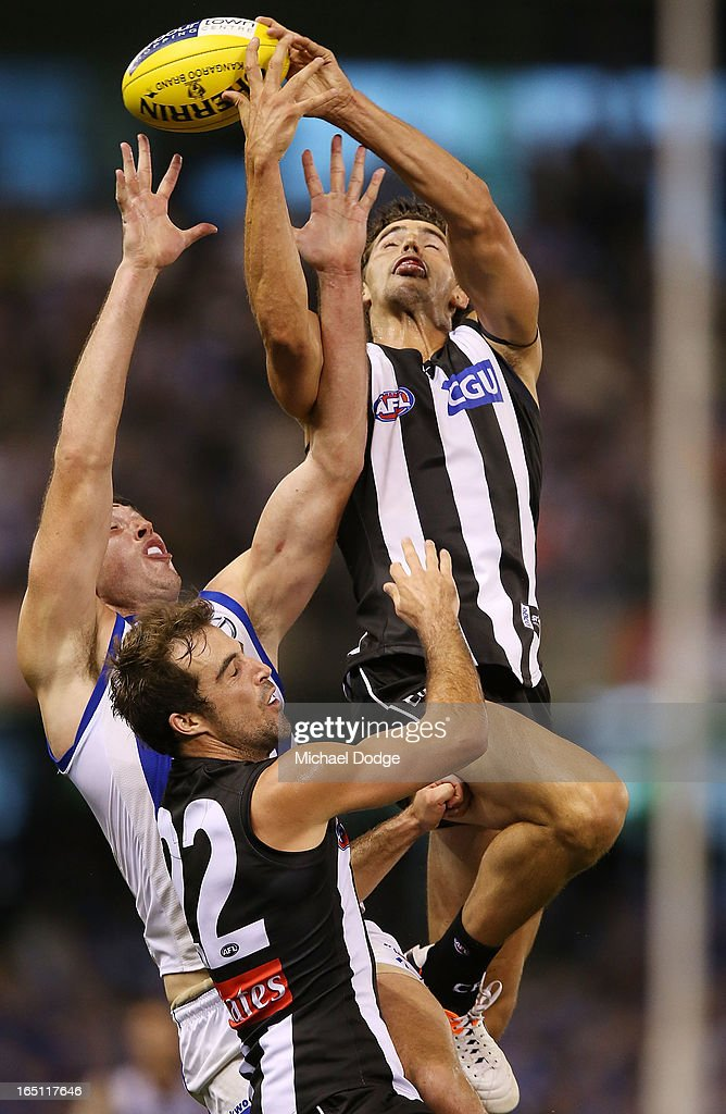 Scott Pendlebury of the Magpies marks the ball over Todd Goldstein of the Kangaroos and teamate Steele Sidebottom during the round one AFL match between the North Melbourne Kangaroos and Collingwood Magpies at Etihad Stadium on March 31, 2013 in Melbourne, Australia.
