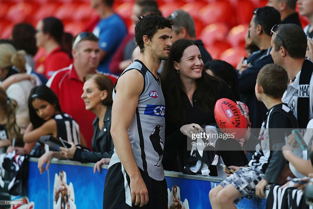 Scott Pendlebury poses for a photograph with fans during a Collingwood Magpies AFL training session at Metricon Stadium on July 19, 2013 in Gold Coast, Australia.
