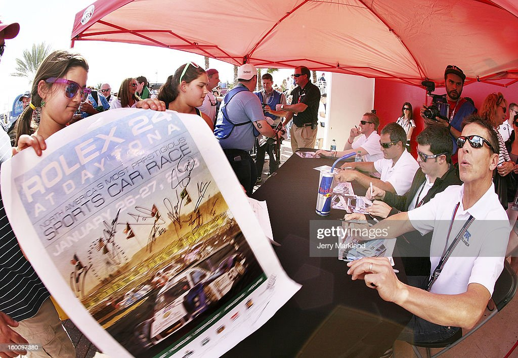 Scott Pruett, co-driver of the #01 Chip Ganassi with Felix Sabates TELMEX/Target BMW Riley signs autographs along with co-drivers Memo Rojas, Juan Pablo Montoya and Charlie Kimbal at the Rolex 24 at Daytona International Speedway on January 26, 2013 in Daytona Beach, Florida.