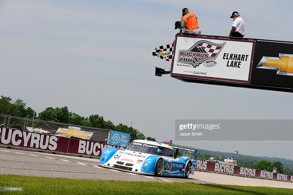 <a gi-track='captionPersonalityLinkClicked' href=/galleries/search?phrase=Scott+Pruett&family=editorial&specificpeople=541449 ng-click='$event.stopPropagation()'>Scott Pruett</a>/<a gi-track='captionPersonalityLinkClicked' href=/galleries/search?phrase=Memo+Rojas&family=editorial&specificpeople=3547976 ng-click='$event.stopPropagation()'>Memo Rojas</a>, drivers of the #01 Chip Ganassi Racing with Felix Sabates BMW Riley crosses the finish line to win the GRAND-AM Rolex Series Road America 250 at Road America on June 25, 2011 in Elkhart Lake, Wisconsin.