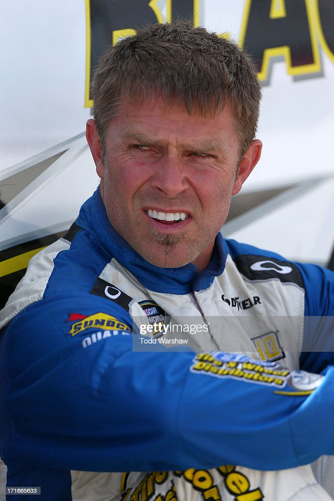 Scott Riggs driver of the Blacks Tire/Fleet HQ/QMI/Davis Tire Chevrolet sits next to his car on the grid during qualifying for the NASCAR Camping...