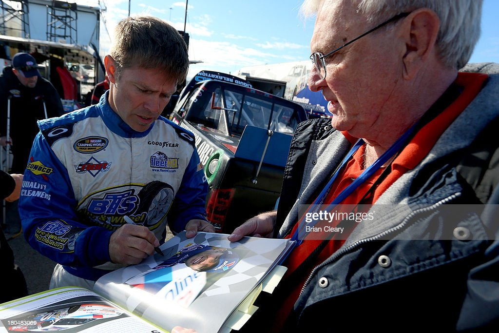 Scott Riggs driver of the CarQuest WorldPac/GoodyearFleetHQ Chevrolet signs an autograph during practice for the NASCAR Camping World Truck Series...