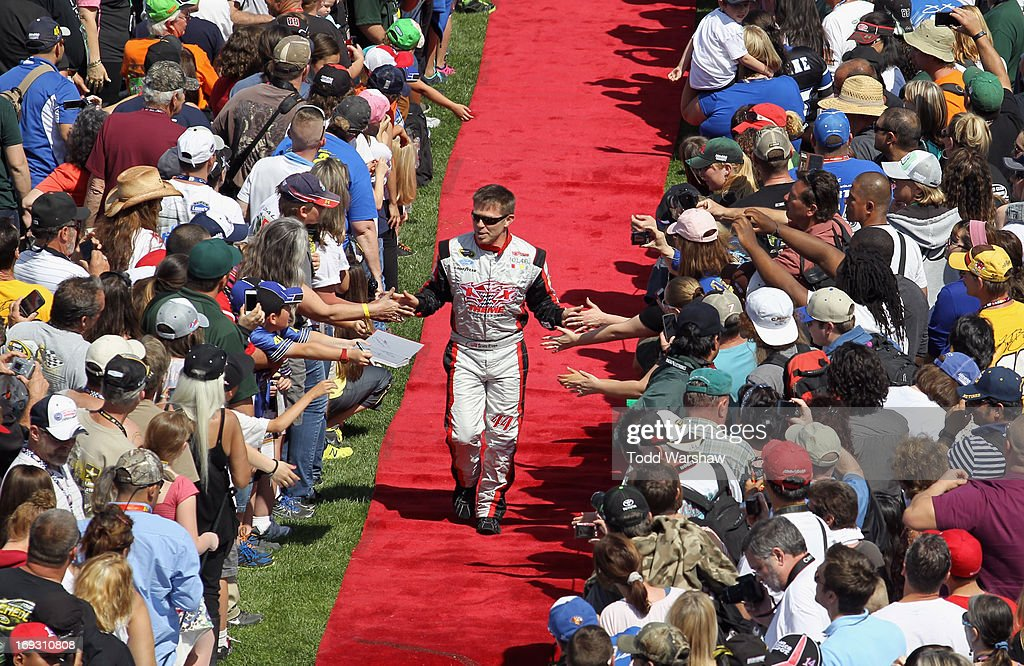 Scott Riggs driver of the No Label Ford greets fans during the NASCAR Sprint Cup Series Auto Club 400 at Auto Club Speedway on March 24 2013 in...