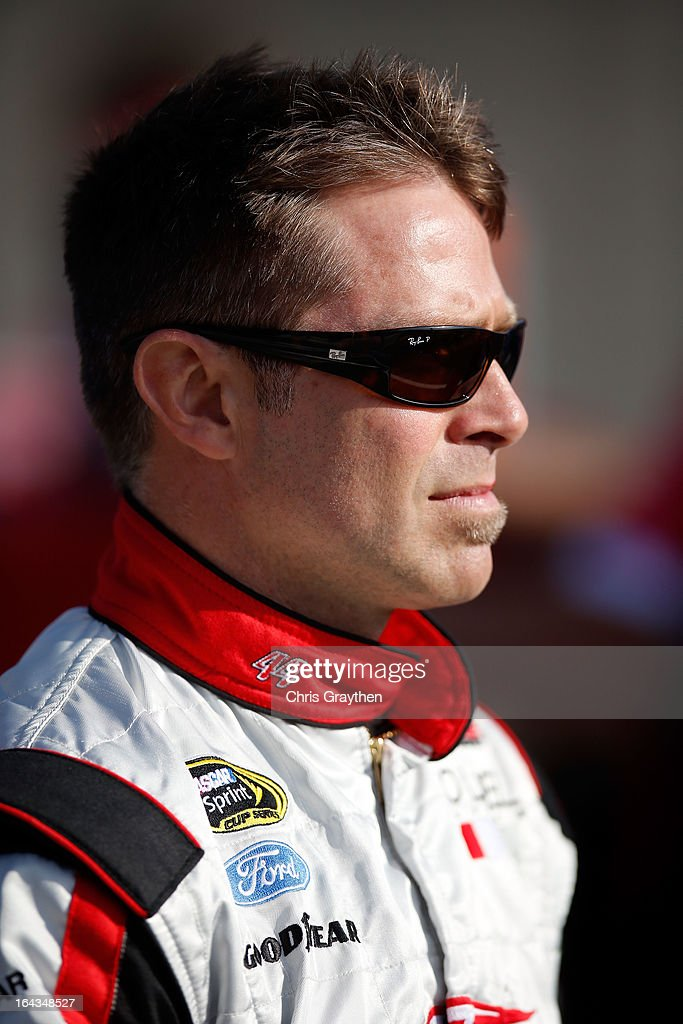 Scott Riggs driver of the No Label Ford stands on the grid during qualifying for the NASCAR Sprint Cup Series Auto Club 400 at Auto Club Speedway on...