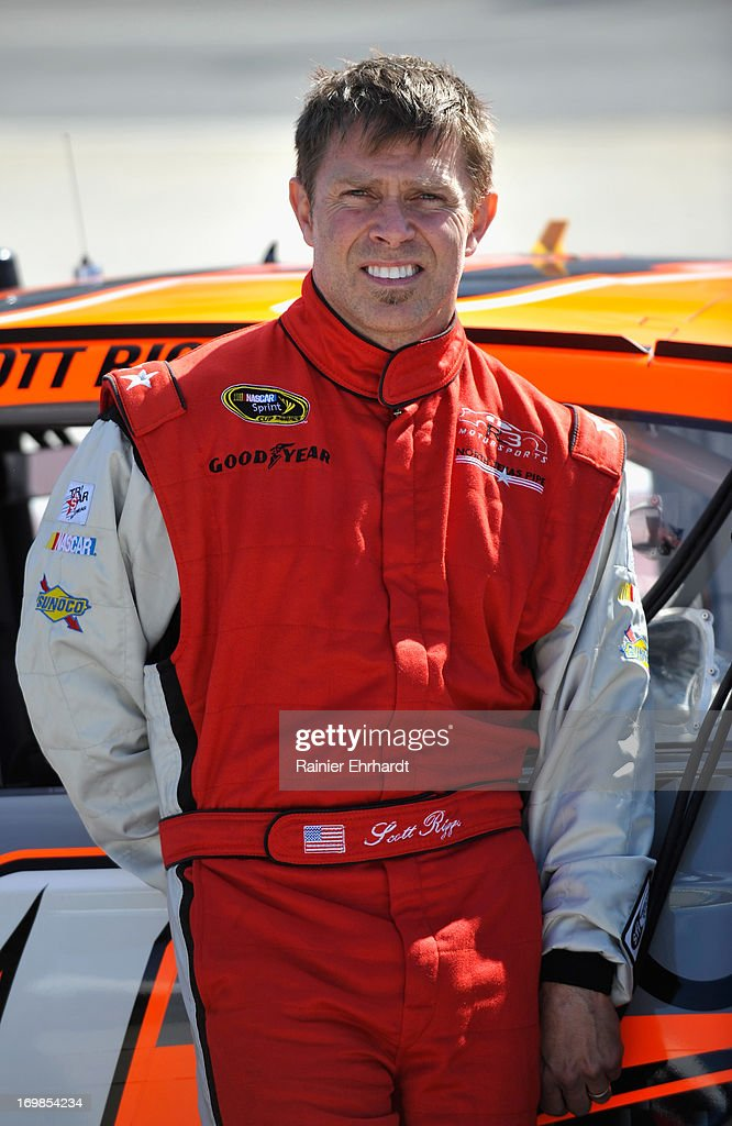 Scott Riggs driver of the No Label Watches Ford waits by his car during qualifying for the NASCAR Sprint Cup Series STP Gas Booster 500 on April 5...