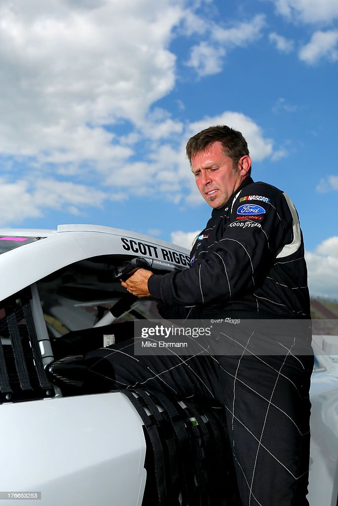 Scott Riggs driver of the Plinker Tactical Toyota climbs from his car after qualifying for the NASCAR Sprint Cup Series 44th Annual Pure Michigan 400...