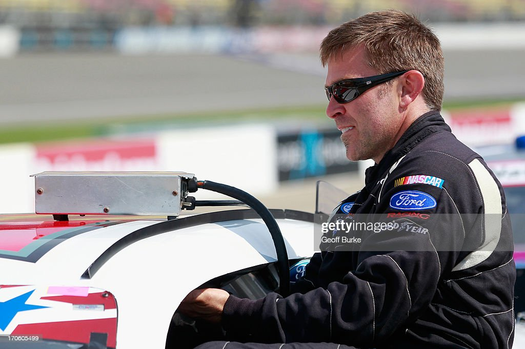 Scott Riggs driver of the Rick Ware Racing Ford climbs into his car during qualifying for the NASCAR Nationwide Series Alliance Truck Parts 250 at...