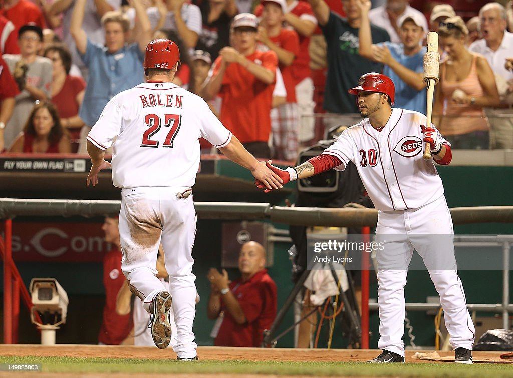 <a gi-track='captionPersonalityLinkClicked' href=/galleries/search?phrase=Scott+Rolen&family=editorial&specificpeople=167236 ng-click='$event.stopPropagation()'>Scott Rolen</a> #27 of the Cincinnati Reds is congratulated by <a gi-track='captionPersonalityLinkClicked' href=/galleries/search?phrase=Dioner+Navarro&family=editorial&specificpeople=593062 ng-click='$event.stopPropagation()'>Dioner Navarro</a> #30 after scoring the game winning run in the 5-4 victory over the Pittsburgh Pirates at Great American Ball Park on August 4, 2012 in Cincinnati, Ohio.