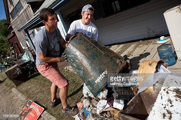 Scott Salway and Mark Cascardi dump out mud and debris from a real estate office that was flooded in tropical storm Irene on West Main Street on...