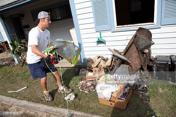 Scott Salway removes debris from a real estate office that was flooded in tropical storm Irene on West Main Street on August 31 2011 in Wilmington...